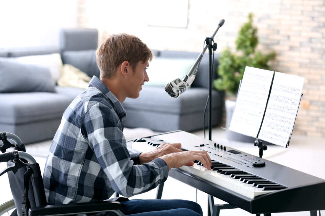 Young musician in wheelchair playing piano at home