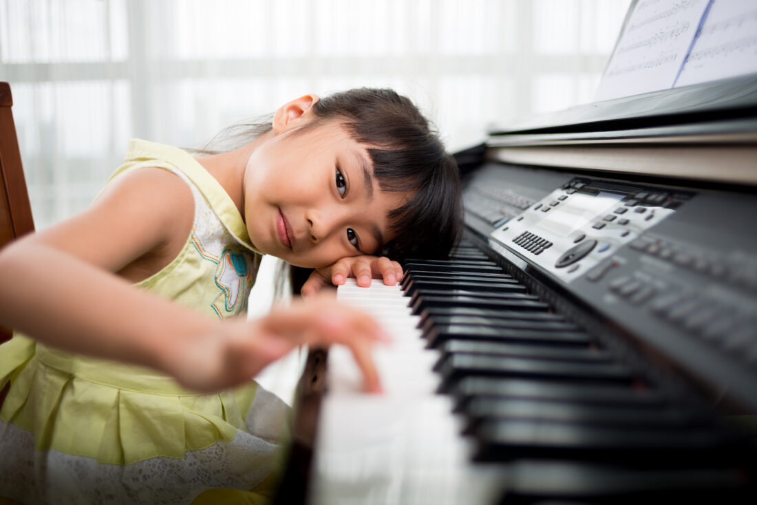 Little Vietnamese girl tentatively playing the piano and looking,at the camera