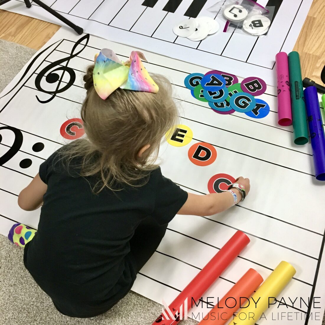 Young piano student composing with the giant floor staff