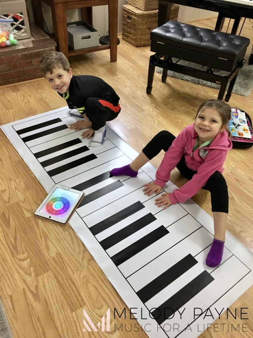 Young piano students playing piano key twister