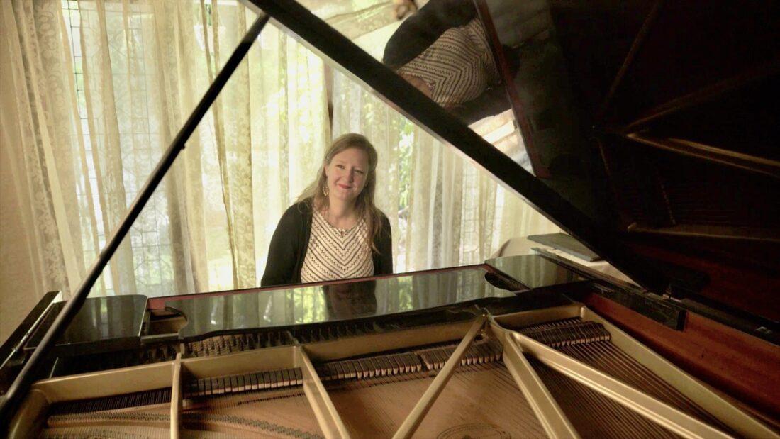 Melanie Hardage sitting at her piano
